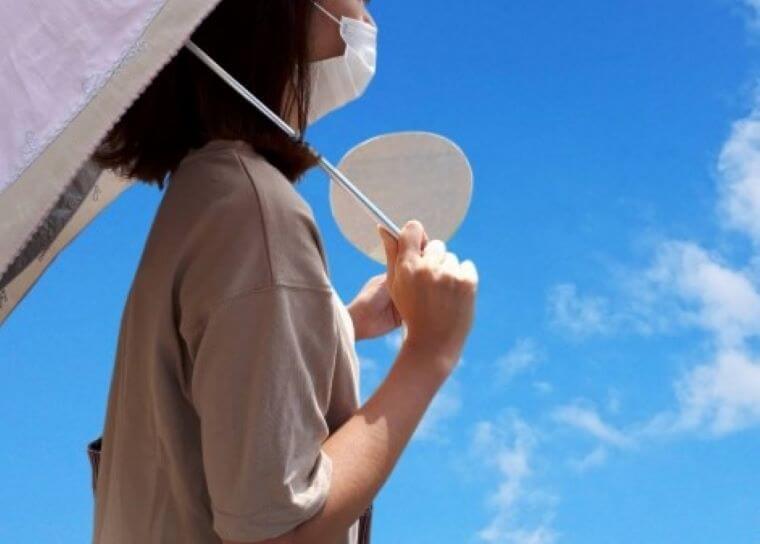 マスク姿で日傘をさす女性
